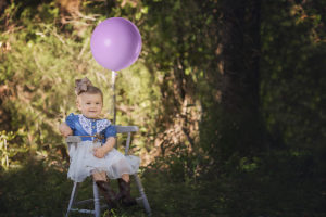 everly turns one | one year old sitting in antique chair with pink balloon {santa rosa beach photographer}