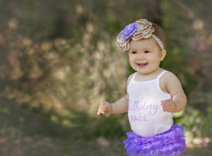 everly turns one | one year old smiling with her birthday onesie and purple laced bloomers {destin, florida photographer}