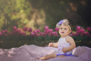 everly turns one | baby girl sitting in front of pink tulips in the garden {30a newborn photographer}