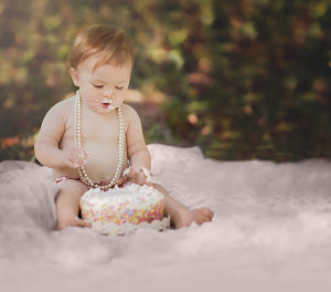 everly turns one | baby girl enjoying her cake smash on a pink blanket outdoors {tallahassee newborn photographer}